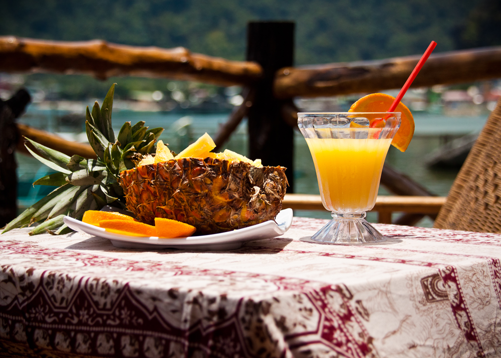 Table on guesthouse porch set with orange juice and pineapple