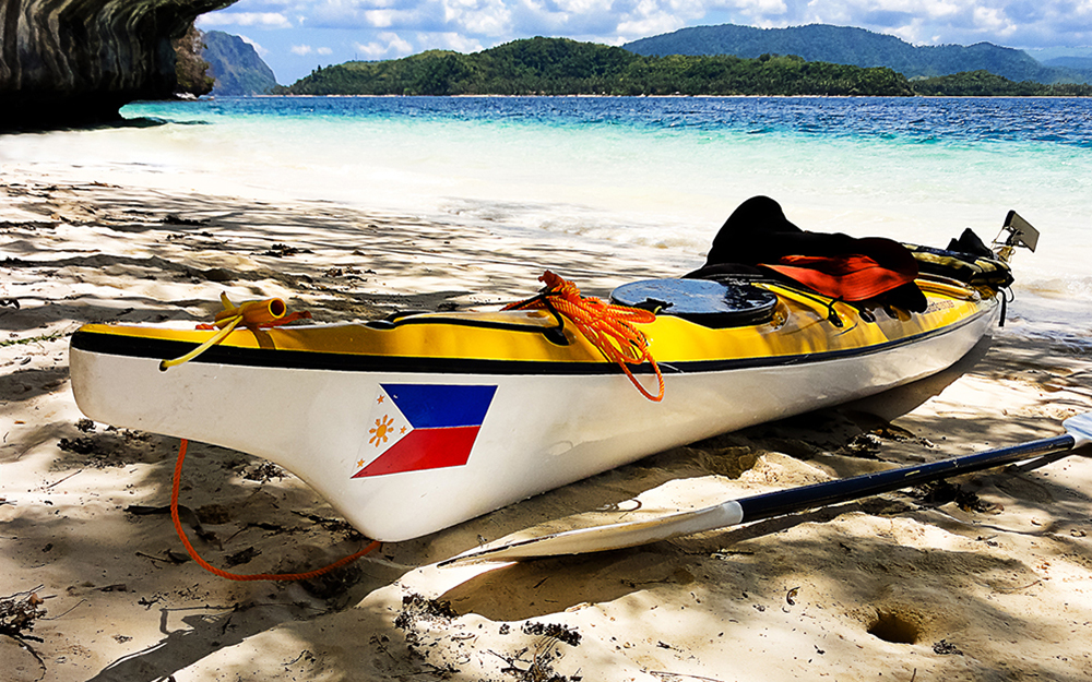 Kayak on sunny beach with cliffs in background