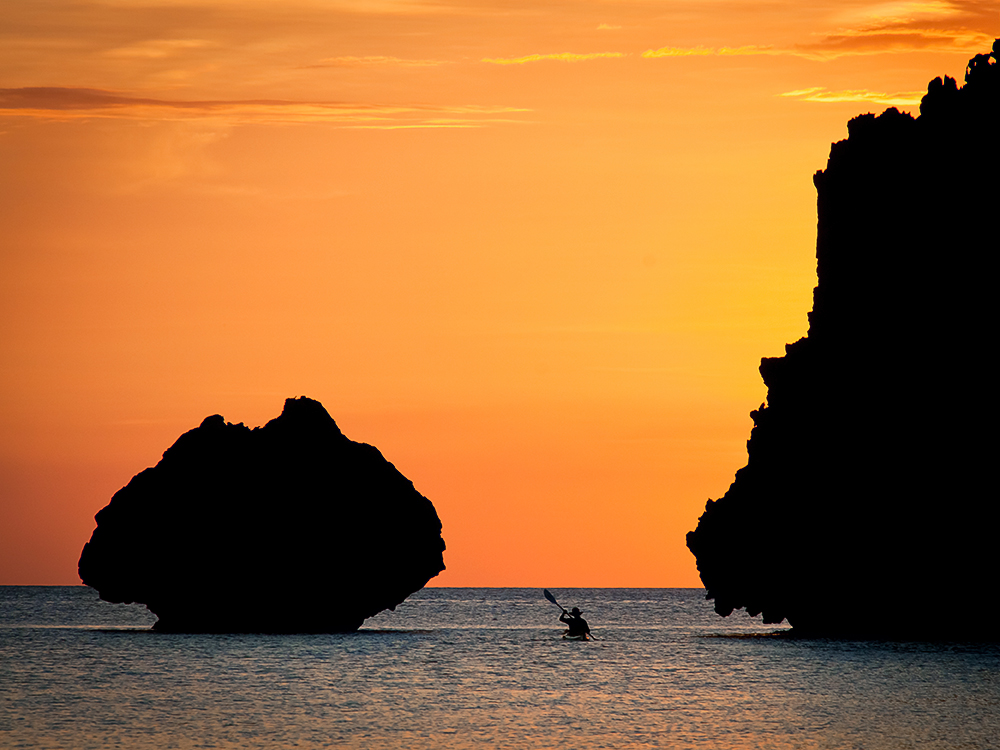 Kayaker paddling between cliffs toward orange sunset